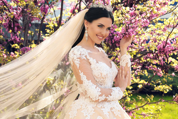 fashion outdoor photo of gorgeous bride in luxurious wedding dress, posing in blossom garden