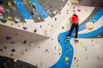 Active young climber woman climbing on indoor climbing wall