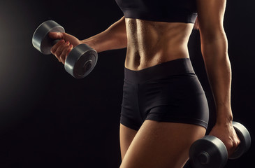 Beautiful fitness woman lifting dumbbells . Fitness sporty woman showing her well trained body . A...