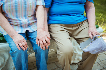 close-up of hands of elderly men and women. Senior couple sitting on a park bench with walking stick.