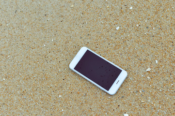 Closeup on smartphone on the beach. Top view flat lay style