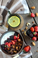 Yogurt with baked granola and berries in small bowl, strawberries,blackberries. Cup of tea with lemon. Granola baked with nuts and honey for little sweetness. Homemade granola
