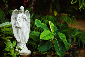 Marble statue of angel with closed eyes at green summer garden