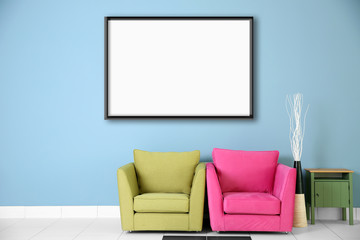 Two armchairs and empty picture frame on blue wall background