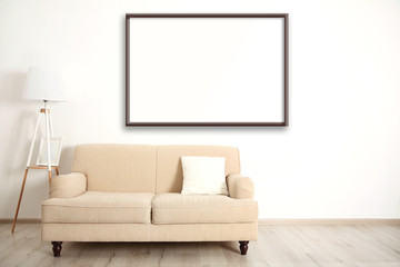 Beige couch with lamp and empty picture frame on wall background