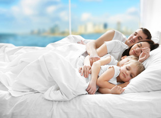 Family sleeping in bed on blurred background