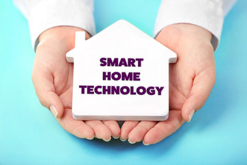 Smart home technology concept. Female hands holding house on turquoise background