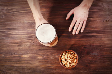 Male hand holding glass of beer on wooden background. Retro stylization