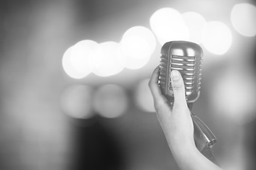 Retro microphone in female hand on abstract blurred background