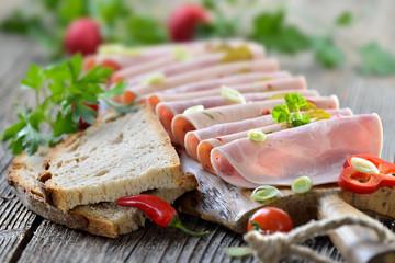 Deftige Wurstbrotzeit mit Bierschinken und Paprikawurst rustikal mit frischem Landbrot serviert - Slices of Bavarian sausages on a rustic wooden board