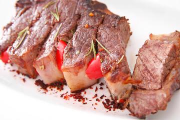 Sliced roasted pork steak on white plate, close up