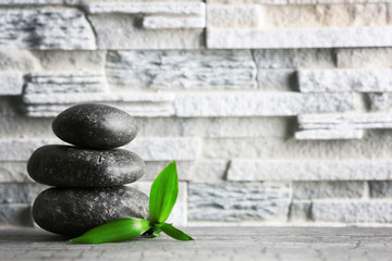 Composition of spa pebbles and bamboo leaf on grey wall background