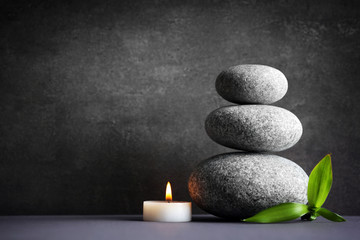 Composition of spa pebbles, candle and bamboo leaf on grey background
