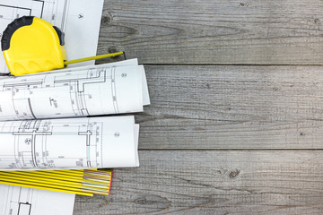 rolls of architectural blueprints and measurement tools on gray