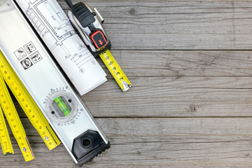 blueprint rolls with tape measure and folding rule on wooden tab