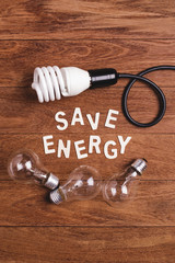 """Energy saving lamp and incandescent lamp and """"save energy"""" word on wooden background. Concept for saving energy. Concept for eco-friendly. Concept for global warming."""