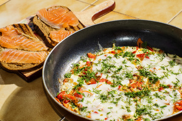 Omelet with tomatoes, cheese and dill and sandwiches with salmon