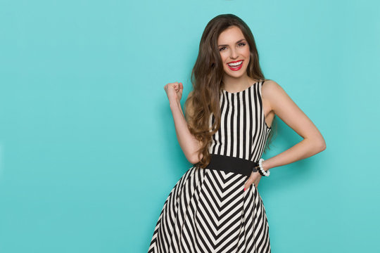 Smiling girl in black and white striped dress posing with fist raised and looking at camera,
