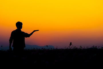 Silhouette of man posing at sunset sky background.