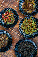 Different kinds of tea on plates on wooden background. Assortment of dry tea. Tea concept. Tea leaves. Top view.