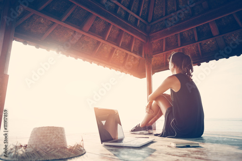 Woman freelancer listening music at sunrise near ocean in shadow shelter. Intentional sun glare and vintage color