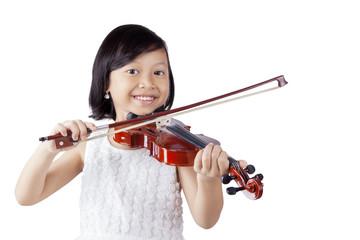 Cheerful girl playing violin in the studio