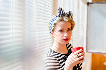 beautiful blond funny pinup woman drinking coffee at home
