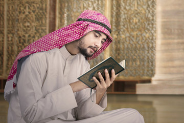 Muslim man sits in mosque and reads Quran