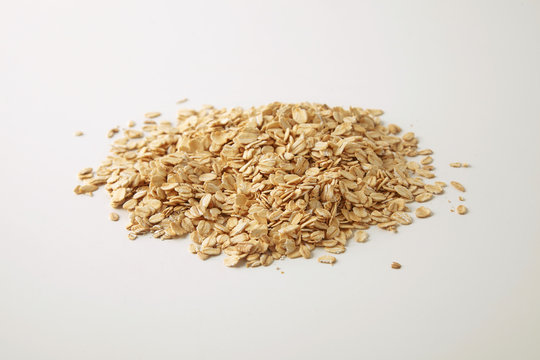 Healthy diet rolled oats isolated on white in center, prepared for cooking muesli for breakfast, side close focus view
