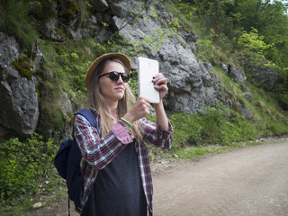 Young hipster woman taking photos with a tablet in the mountain.