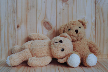 Two teddy bears sitting together on wooden background. Snuggle. Friendship concept. Love concept. Greeting card on wood.