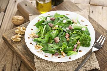 Feldsalat mit Speckwürfeln und Walnüssen auf weißem Teller angerichtet
