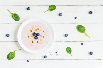blueberry yogurt with muesli on the plate on wooden white background, top view, flat lay
