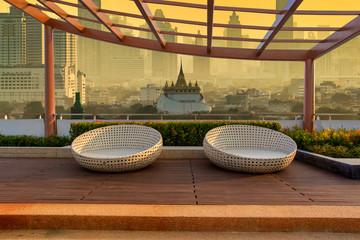 Relax corner on condominium rooftop garden with chairs on landmark bangkok Golden Mount Temple in the sunrise time background, Landmark concept