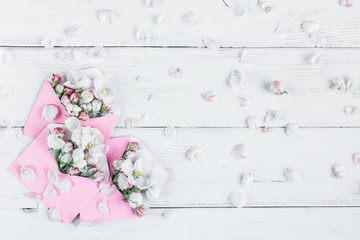 pink envelopes with flowers on white wooden background, flat lay, top view