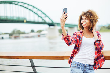 Young woman standing at the balcony and taking selfie