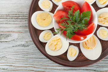 Boiled hen eggs and red tomato