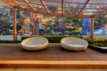 Relax corner on condominium rooftop garden with chairs on landmark bangkok top view at night background, Landmark concept