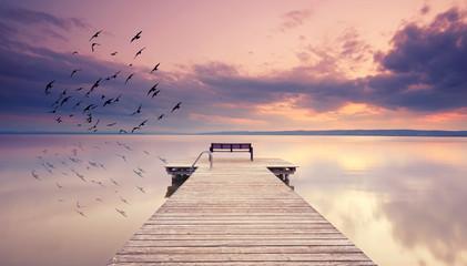 alter Holzsteg mit Bank am See zum Sonnenuntergang