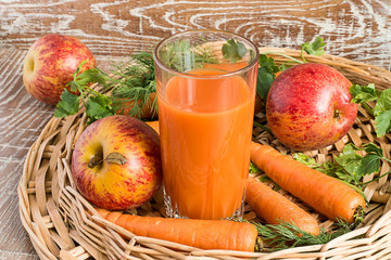 Juice, apples and carrots.    A glass with juice, fresh apples and carrots in a wicker basket on a brown wooden background.
