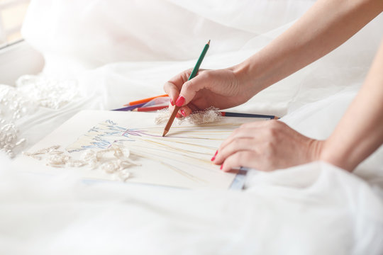 Cheerful female tailor is creating bridal gown