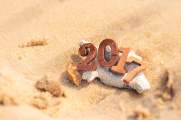 Wood number 2017 on beach background idea, happy new year concept