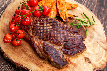 Grilled Beef Sirloin Steak on wooden board with vegetables.