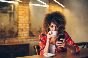 Young woman at cafe drinking coffee and using mobile phone