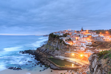 Azenhas do Mar village at dusk with stormy sea and dark clouds,