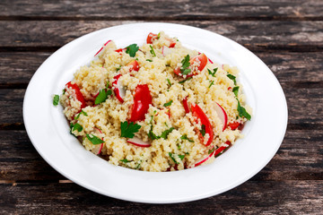 Homemade Fresh Couscous salad with vegetables, in white plate.