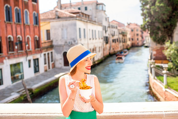 Young female traveler eating traditional italian bolognese pasta to go on the bridge in Venice. Image with small depth of field