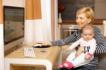 Young mother using computer while holding baby