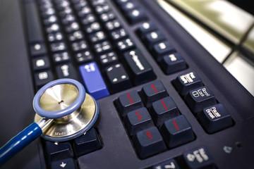 blue stethoscope on black keyboard of physician