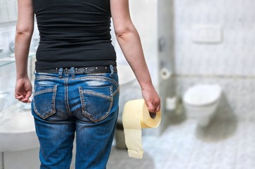 Woman suffers from diarrhea holds toilet paper in hand in restroom.
